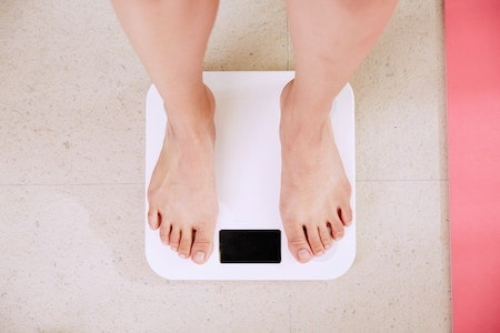Person weighing themselves- lose weight without exercise
